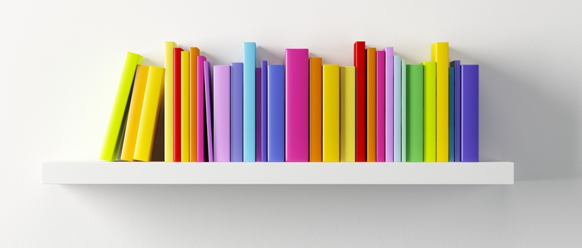 coloured books on bookshelf with white wall behind