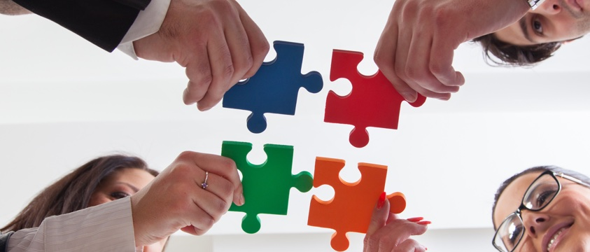 four colourful jigsaw pieces held close together, photo taken from below