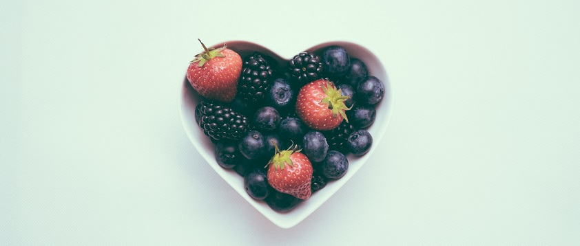 A stock image of a heart-shaped fruit bowl with fresh berries.