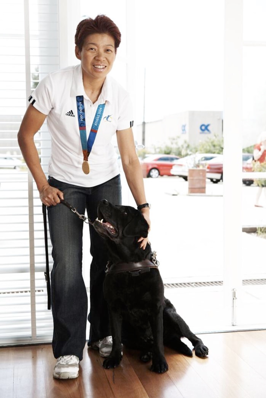 woman in track pants, T-shirt, with black guide dog