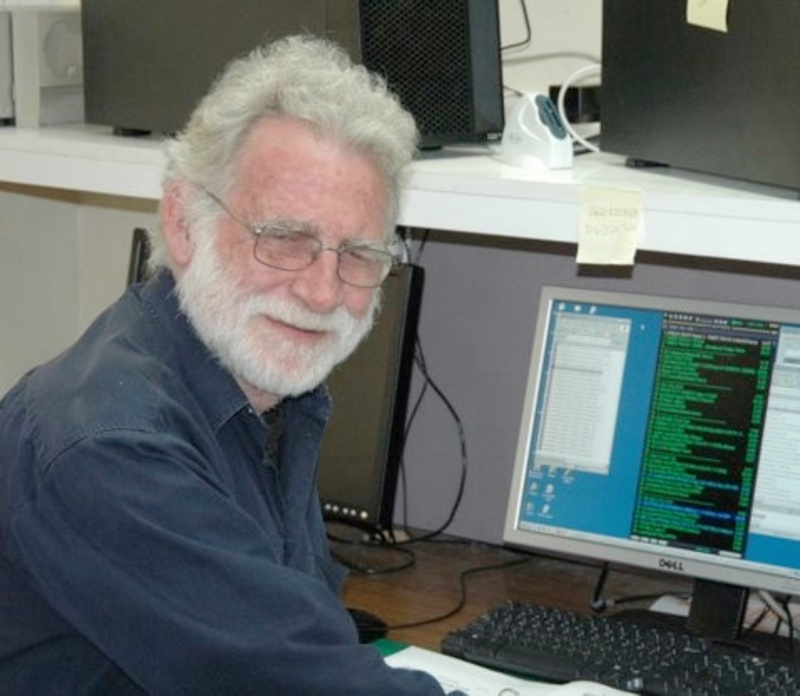 smiling white haired and bearded man, turning from computer scrren