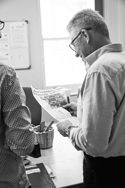A black and white photo of a 2RPH volunteer reading the newspaper.