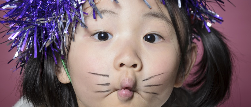 girl with purple glitter in hair and cat make up