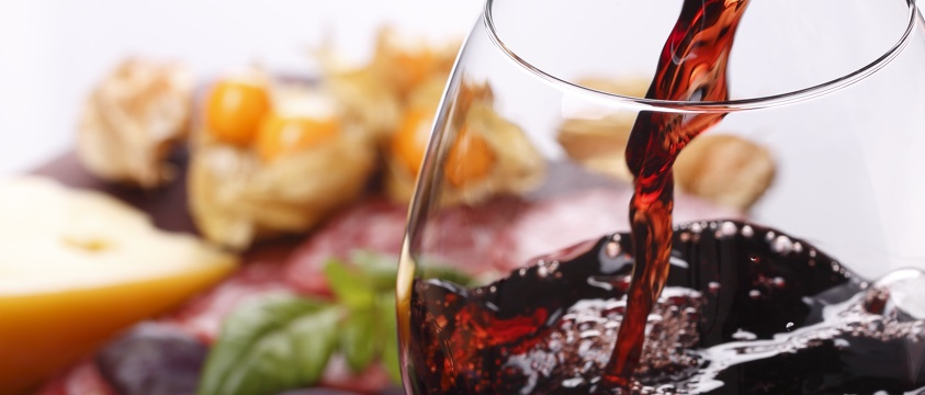 red wine poured into glass, fine food in background