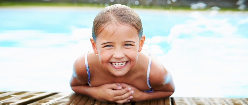 7-year old girl at edge of swimming pool, big grin