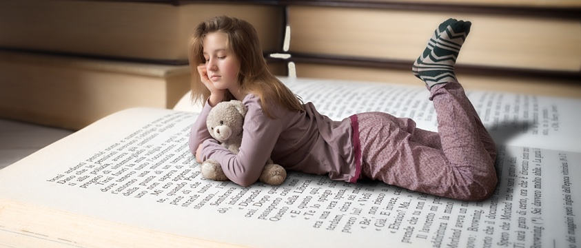 girl in pyjamas, holds teddy, lies on huge book, reading