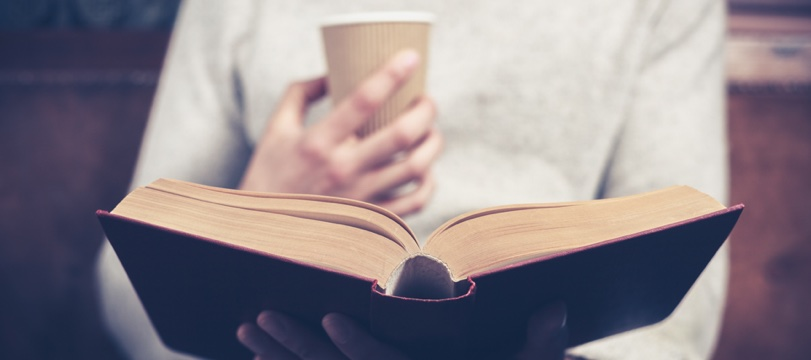 closeup person with coffee in disposable cup reads book