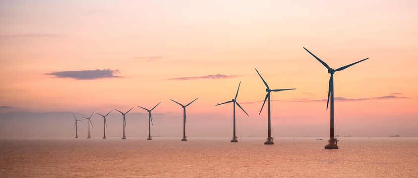 wind turbines at sea on horizon