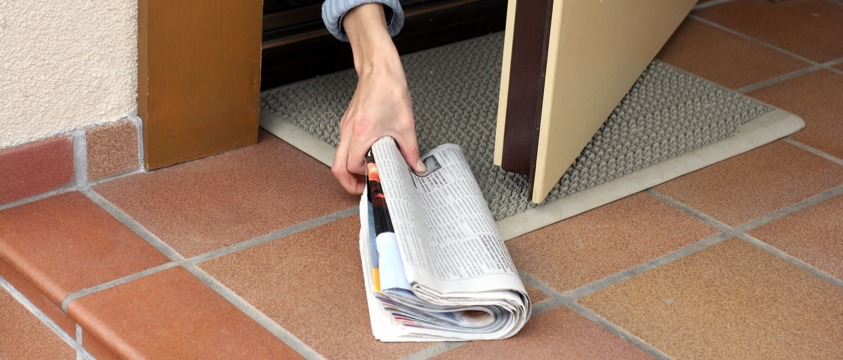 close up woman picks up from doorstep newspaper with magazine inside