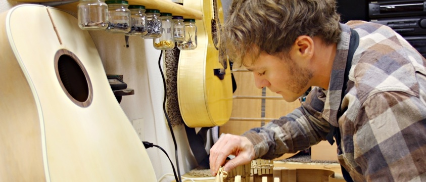 young man builds wooden guitar