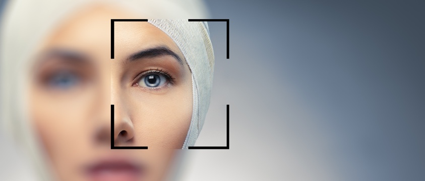 out of focus woman with bandage on head looks through square frame with clear eye in focus