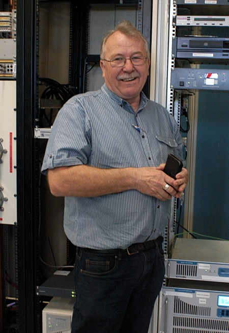 three quarter photo of smiling man, moustache, holding equipment, in front of racks of equipment